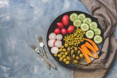 La nourriture végétale végétarienne a servi d'un plat noir, fond gris, vue supérieure, l'espace de copie Photo stock