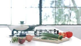 La nouvelle poêle sur le miroir faisant cuire le plat dans l'intérieur blanc Les légumes frais se trouvent près d'une poêle sur u Photos libres de droits