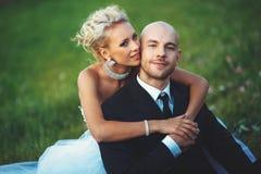 La novia abraza suavemente al novio que se sienta en el césped Imagen de archivo libre de regalías