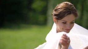 La novia adorable con el pelo oscuro y la sonrisa bonita está haciendo girar alrededor de y está jugando con su velo blanco perfe almacen de video