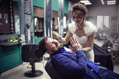La novia afeita al novio con una maquinilla de afeitar recta foto de archivo libre de regalías