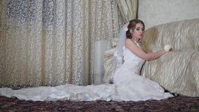 La novia apacible se sienta con una rosa en el piso cerca del sofá almacen de metraje de vídeo