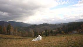 La novia atractiva joven en el vestido de boda elegante está corriendo a lo largo del prado de oro en las montañas metrajes