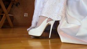 La novia aumenta pies de descubrimiento del vestido de boda en primer de los zapatos de las medias