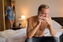 La novia cogió a su novio de engaño mientras que él el ` s en el teléfono con otra mujer foto de archivo
