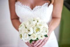 La novia con el ramo hecho con el loto poner crema blanco y las rosas florecen, se centran en el ramo - cerrado para arriba Foto de archivo