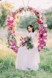 La novia con los accesorios del pelo que sostienen el ramo de peonías, mirando la tierra y sentándose en la boda Foto de archivo libre de regalías