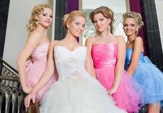 La novia con sus damas de honor en las escaleras Fotos de archivo libres de regalías