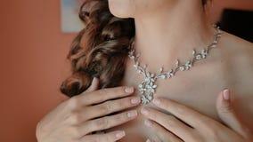 La novia con un peinado de la boda ajusta los ornamentos en un cuello Preparación para la celebración metrajes