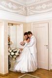 La novia de abarcamiento del novio cerca del espejo Foto de archivo libre de regalías