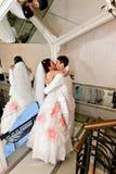 La novia de abarcamiento del novio cerca del espejo Fotos de archivo