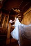 La novia de la belleza en vestido nupcial con el ramo y el cordón velan dentro Foto de archivo