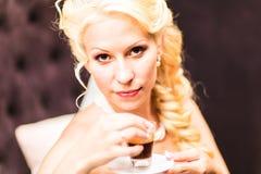 La novia de la belleza en vestido nupcial está bebiendo té dentro Muchacha modelo hermosa en un vestido de boda blanco Retrato fe Fotos de archivo