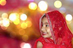 La novia de niño en sari roja y el bokeh se encienden en fondo Imagen de archivo