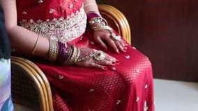 La novia del primer en silla lleva a cabo las manos con Henna Patterns en rodillas