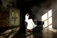 La novia en el vestido blanco que se sienta en silla dentro en interior oscuro del estudio tiene gusto en casa Fotos de archivo