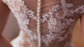 La novia en el vestido de boda blanco sostiene un ramo