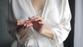 La novia en la bata de seda blanca se sostiene en sus anillos de bodas de la mano dos almacen de metraje de vídeo