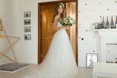 La novia en un vestido de boda hermoso con un pelo rizado largo se coloca en el dormitorio y mira la cámara foto de archivo libre de regalías