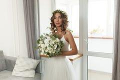 La novia en un vestido de boda hermoso con un pelo rizado largo se coloca en el dormitorio y mira la cámara fotografía de archivo libre de regalías
