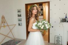La novia en un vestido de boda hermoso con un pelo rizado largo se coloca en el dormitorio y mira la cámara fotografía de archivo
