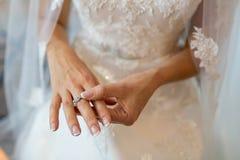 La novia en un vestido que se casa con un velo que lleva un anillo de plata en el dedo medio imagen de archivo libre de regalías