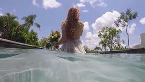 La novia en un vestido que se casa en la piscina en un chalet tropical Subacuático almacen de metraje de vídeo