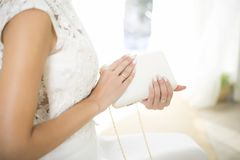 La novia en un vestido que se casa sostiene a disposición un bolso blanco Manicura hermosa Día de boda Anillos de bodas fotos de archivo