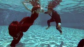 La novia en un vestido rojo y el novio en una nadada del traje bajo el agua en la piscina, y el fotógrafo los toma contra almacen de metraje de vídeo