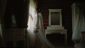 La novia en una bata de seda blanca camina a lo largo de la ventana panorámica en la casa de madera almacen de metraje de vídeo
