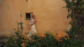 La novia encantadora camina en el jardín hermoso con las flores amarillas del crisantemo almacen de video