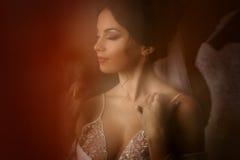 La novia encantadora coloca el vestido de boda cercano en el cuarto Imágenes de archivo libres de regalías