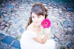 La novia encantadora con una flor. Imagen de archivo libre de regalías