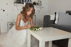 La novia encantadora en el vestido de boda blanco prepara sus accesorios para la ceremonia de boda Una muchacha se hace una guirn Imagen de archivo