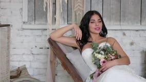 La novia es una morenita hermosa, miente en un sofá en un interior hermoso en el estilo de un boho metrajes