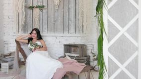 La novia es una morenita hermosa, miente en un sofá en un interior hermoso en el estilo de un boho almacen de metraje de vídeo