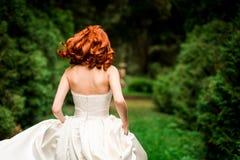 La novia está corriendo en el parque Fotos de archivo libres de regalías
