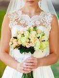 La novia está sosteniendo un ramo delante de ella Imagenes de archivo