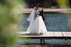 La novia feliz caucásica rubia elegante con el novio está presentando en el th foto de archivo
