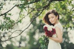 La novia feliz con un ramo de peonías en el fondo empañó el árbol imagen de archivo libre de regalías
