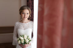 La novia feliz hermosa con la boda florece el ramo en el vestido blanco con el peinado y el maquillaje de la boda Fotografía de archivo libre de regalías