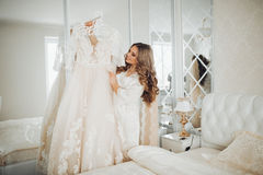 La novia feliz hermosa sostiene el vestido de boda, La muchacha en el cuarto ligero la novia Imagen de archivo
