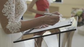 La novia firma el documento en el registriraj de la oficina de registro este día de boda metrajes