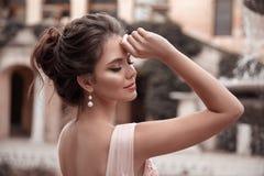La novia hermosa con joyería de los pendientes de la perla lleva el vestido rosado del baile de fin de curso Retrato romántico al foto de archivo libre de regalías