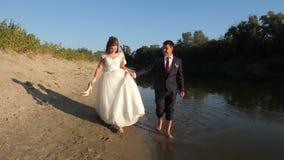 La novia hermosa en el vestido blanco y el novio caminan descalzo en agua a lo largo del borde del riverbank el par de amor va de almacen de metraje de vídeo