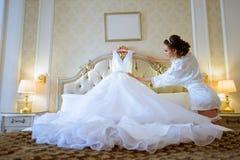 La novia hermosa en traje está mirando un vestido de boda Fotografía de archivo libre de regalías