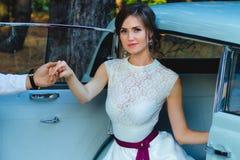 La novia hermosa en vestido de boda sale del coche imagen de archivo libre de regalías