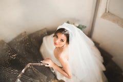 La novia hermosa en vestido magnífico se coloca solamente en las escaleras imagen de archivo