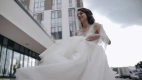 La novia hermosa está caminando alrededor de la ciudad, sosteniendo el dobladillo de su vestido Chica joven hermosa almacen de video