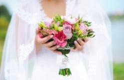 La novia hermosa está sosteniendo un ramo colorido de la boda Belleza de flores coloreadas Manojo del primer de floretes Fotos de archivo